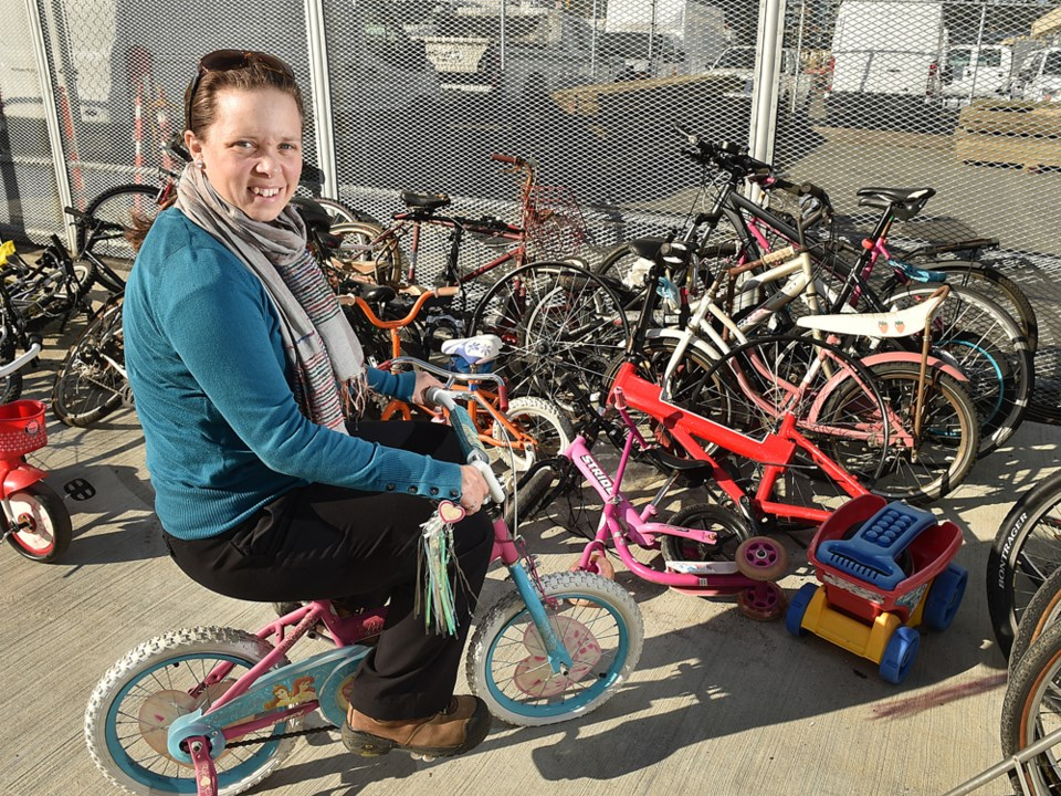 Sarah Willie, a city zero waste manager, with a bicycle dumped at the city's new recycling depot on