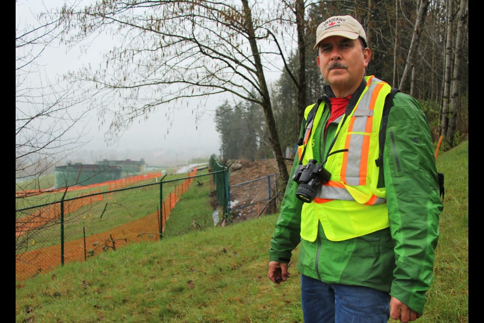 Streamkeeper John Preissl stands north east of Trans Mountain's terminal in Burnaby. Excavation at the site behind him may have led to a sediment spill downstream in Silver Creek.
