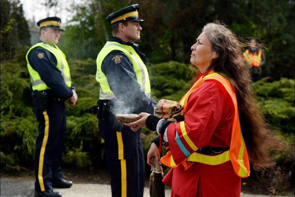 Cynthia Myran burns sage at the protests outside the Trans Mountain terminal.