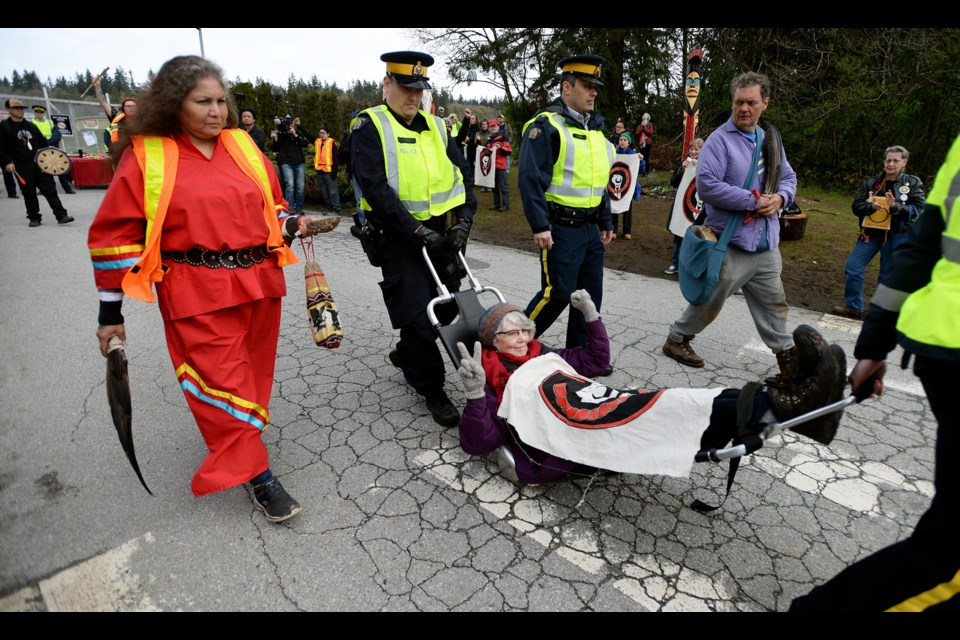 Protester Nan Gregory is carried away by Burnaby RCMP after protesting at the Trans Mountain terminal in Burnaby on Friday.
