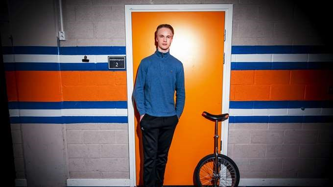 Elias Pettersson standing next to a unicycle.