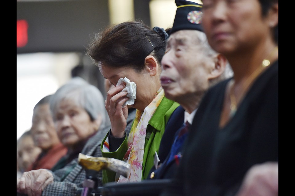 Kelley Lee, seated next to her war veteran father Monty Lee, got emotional Sunday as she listened to an apology from Mayor Gregor Robertson and two former city councillors. Photo Dan Toulgoet