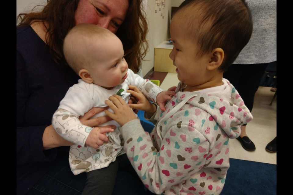 Nine-month-old Natalie and Walter Lee elementary Grade 1 student Kelsey Chen, who is blind, communicate through touch in a Roots of Empathy class. Photo submitted