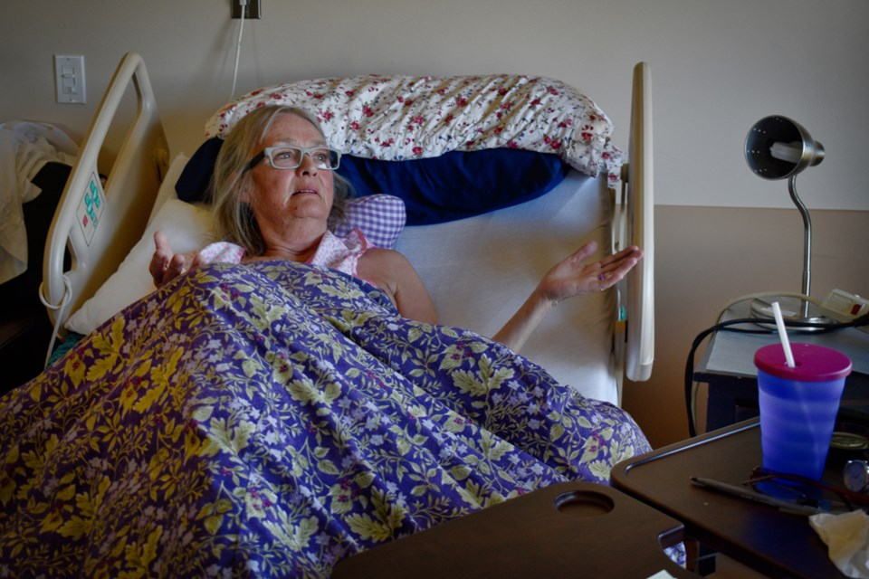 Madeleine Hutchison looks out the window of her room at Mount Peter and Mount Paul. Each patient room at the Marjorie Willoughby Snowden Memorial Hospice Home overlooks Peterson Creek Park.