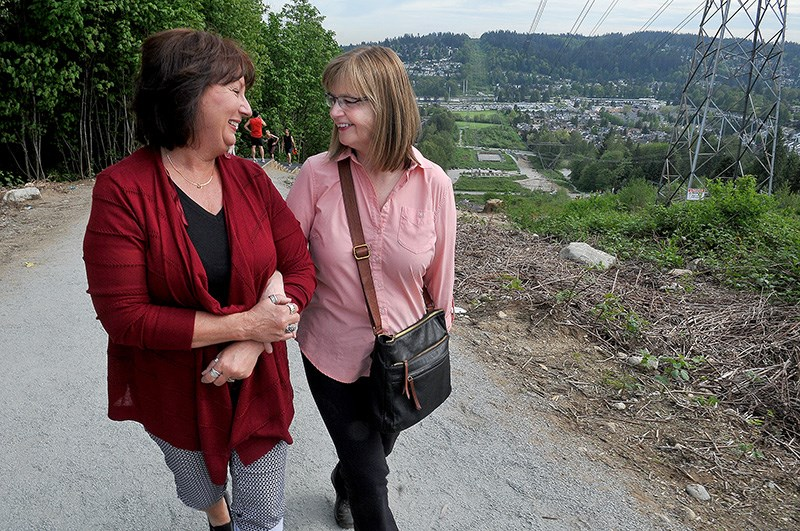 Tammy Bryant (left) and Tanya Leibel share a moment at the top of the stair section of the Coquitlam Crunch on Tuesday. The two women first met when Leibel was having a heart attack on the climb and Bryant, who was hiking with a friend just behind, was able to apply CPR until first responders arrived and took over. They recently reconnected after Leibel posted a sign along the popular hike seeking her saviour.