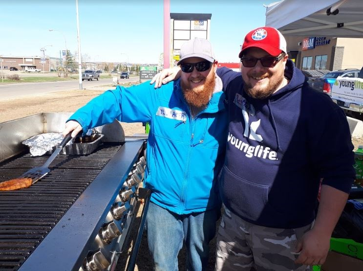 Young Life leaders Bryce Wisekal and Stirling Patterson grill to raise funds for camp.