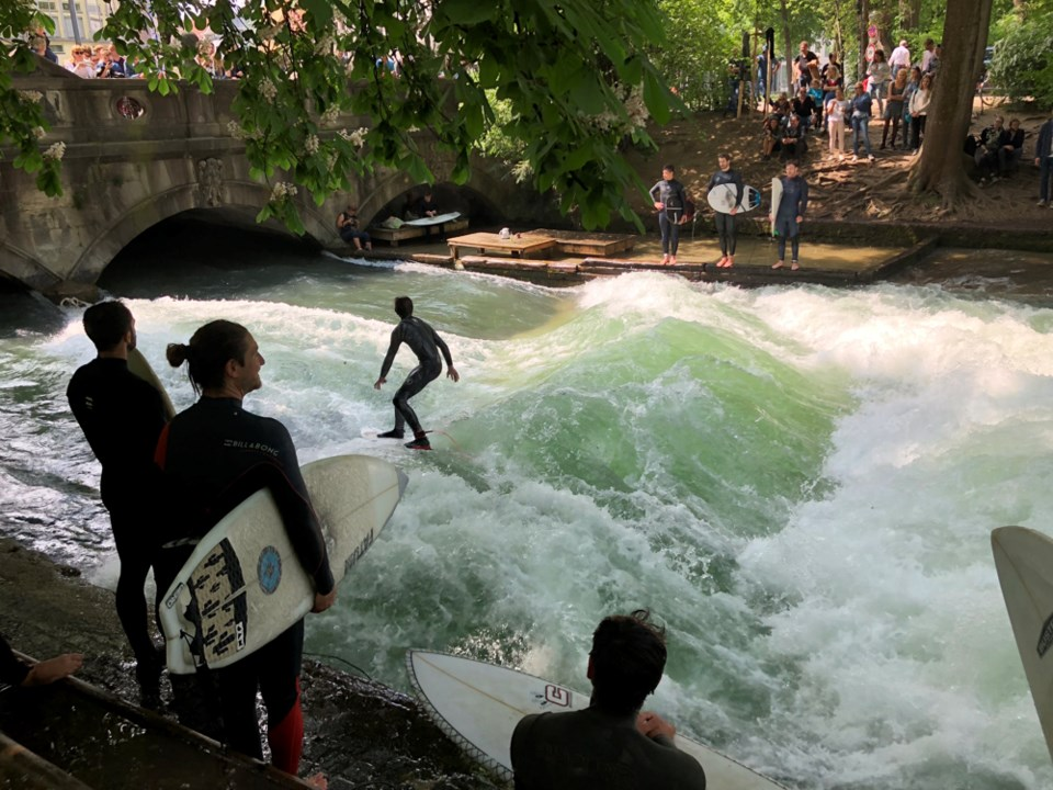 Surfers ride a human-made standing-wave at the Eisbach (German for
