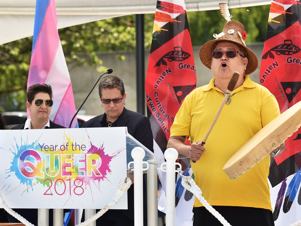 """Fay Nass and SD Holman watch as Stewart Gonzales blesses """"Year of the Queer"""" celebrations."""