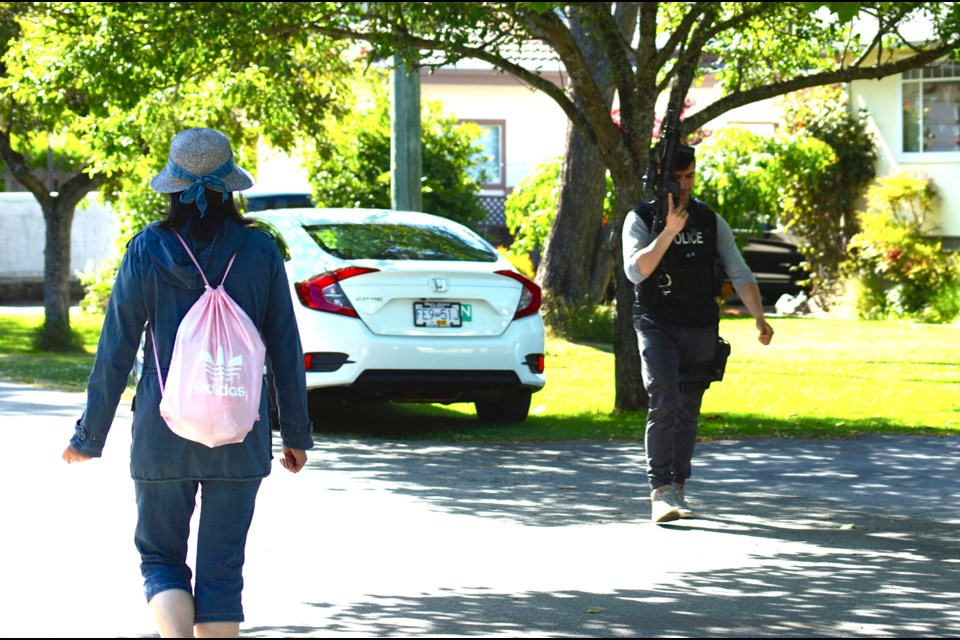 A young woman passes by a heavily-armed police officer on Jasmond Avenue following a police incident May 30 around 2-4 p.m. Graeme Wood photo