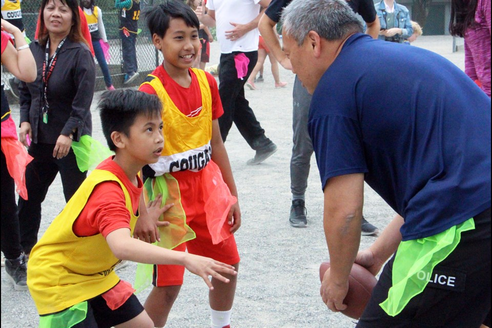 On the run: Lord Kelvin Grade 5 students Rolly Raymundo and Jailan Pagtakhan go head-to-head with New Westminster Police Const. Gerald Lau in last Wednesday's students versus staff football game.