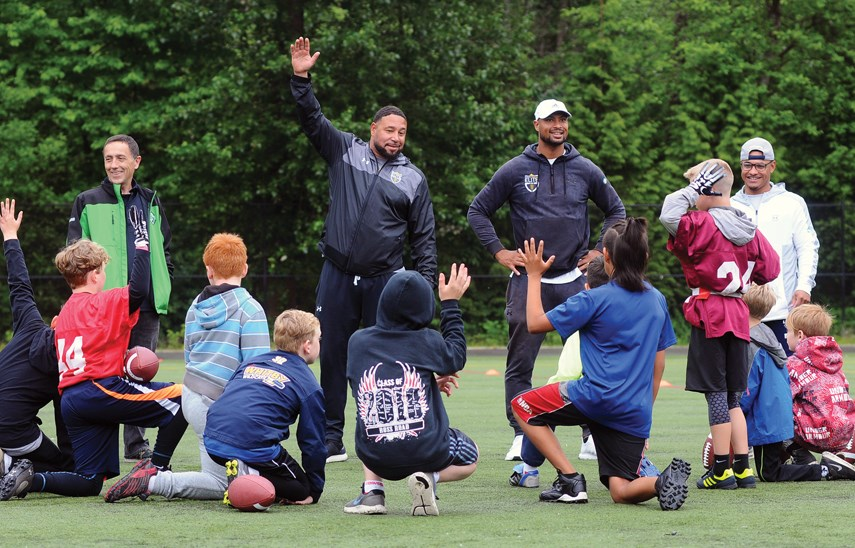 GSL president Mark Currie (left) and former CFL star and North Vancouver native Paris Jackson (white hat) get participants organized for a day of football fun.