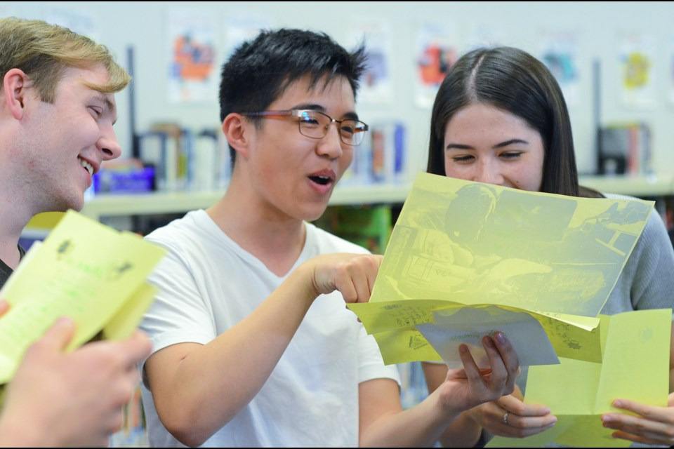 From left, former Seaforth Elementary students Aidan Maddalozzo, Antony Shiu and Mei Doerksen read letters they wrote to themselves in Grade 3. Members of teacher Lynda Glavas's 2006/07 class reunited at Seaforth on June 18 to open a time capsule they sealed 11 years ago.