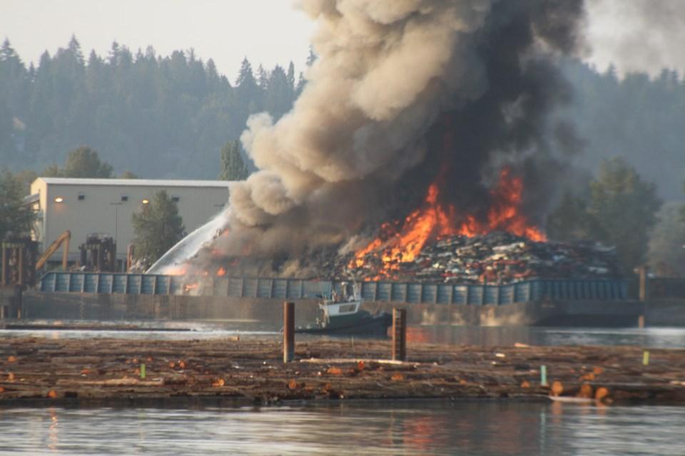 The barge enveloped in flames on the Fraser River.