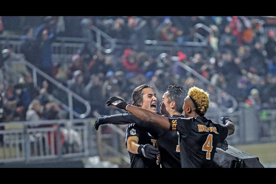 TRU WolfPack teammates James Fraser (from left), Mitch Popadynetz and Josh Banton celebrate a goal at the 2017 U Sports Soccer Championship at Hillside Stadium.