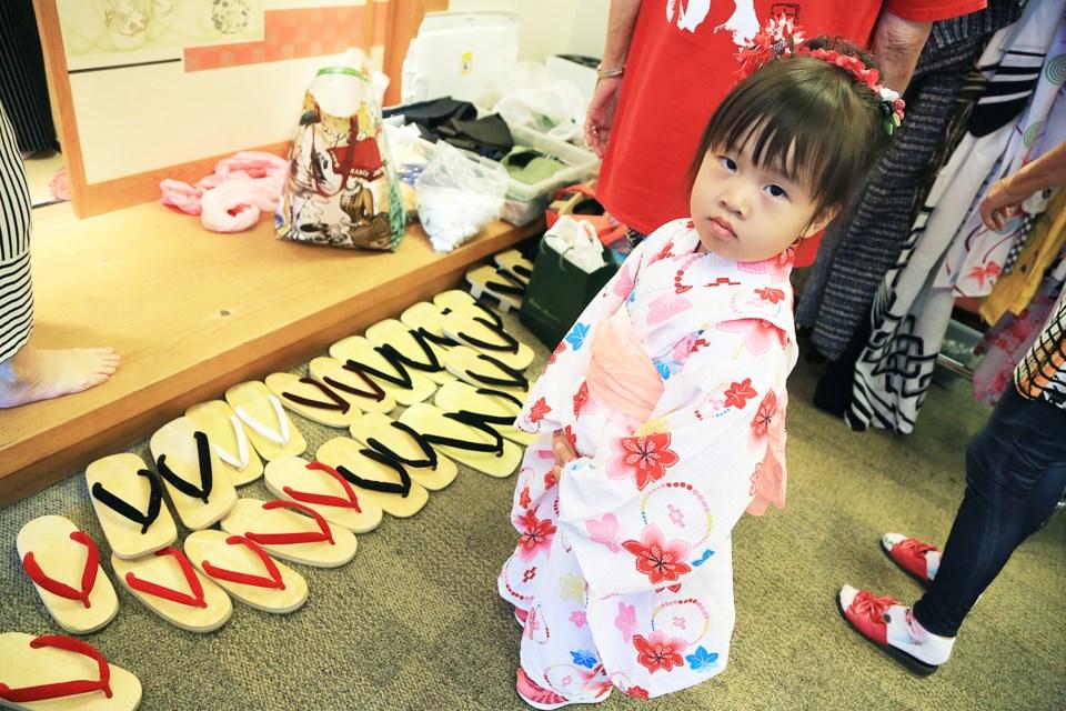 Three-year-old Amber Du tries on a kimono in the kimono dressing area.