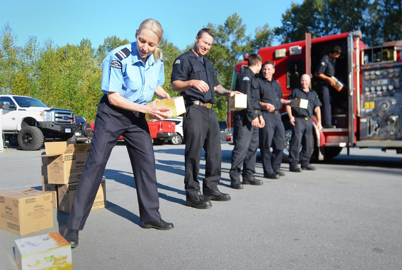 Burnaby firefighters line up to load boxes of food into a truck at Fire Hall 1 earlier this month. Paid for by the Burnaby Firefighters Charitable Society, the snacks are bound for local schools.