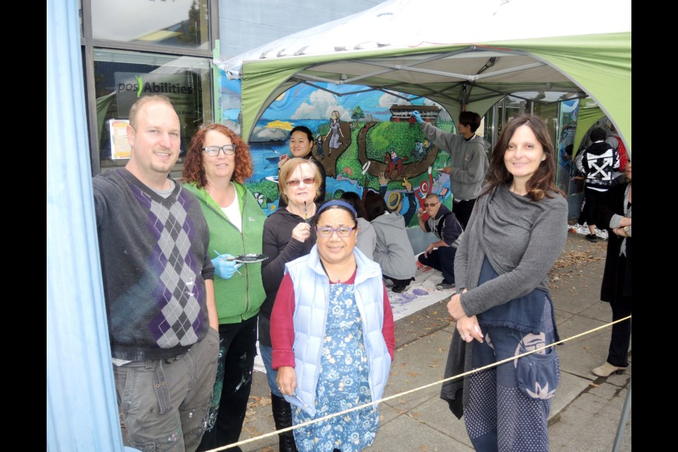 PosAbilities staff and members take a break from painting their community mural. Alan Campbell photos