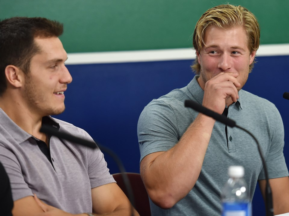 Brock Boeser laughs with Bo Horvat while talking to the media before training camp.