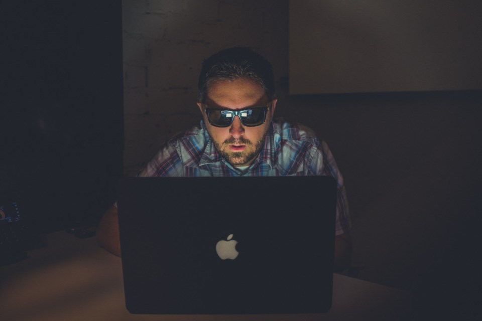 Man at a laptop with sunglasses on