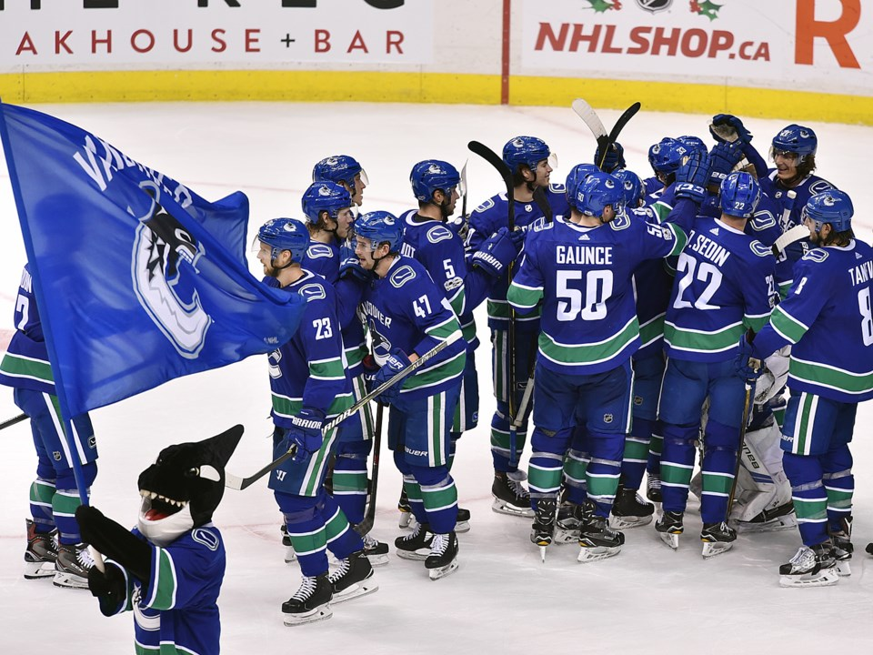Canucks celebrate a victory with Fin