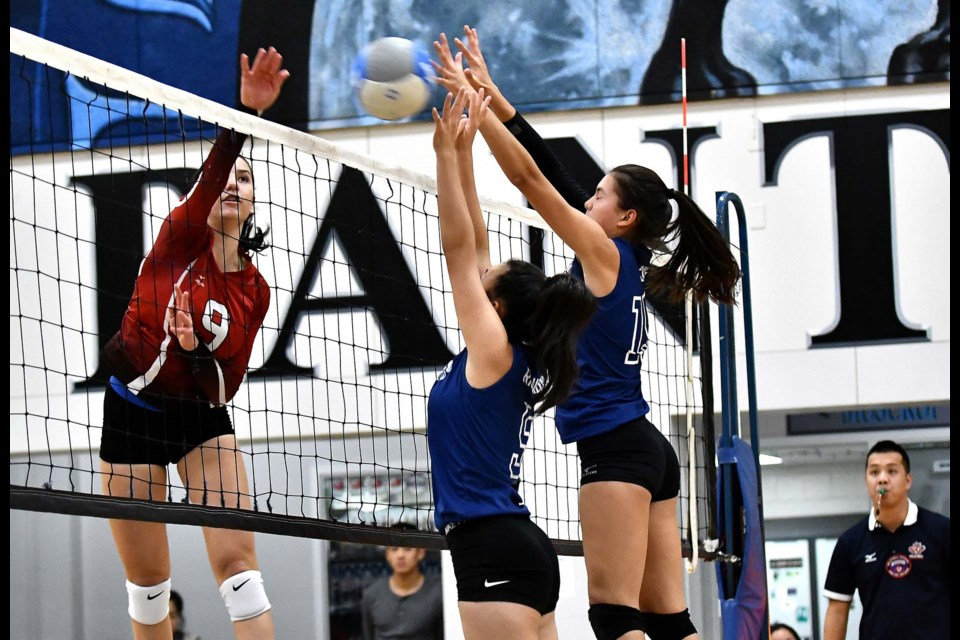 Playing a strong net game, Moscrop senior Panthers' Madeleine Richardson, left, and Alana Leung put their hands up to block junior national team member and Lord Byng power Katarina Pantovic during Saturday's Lower Mainland championship final.