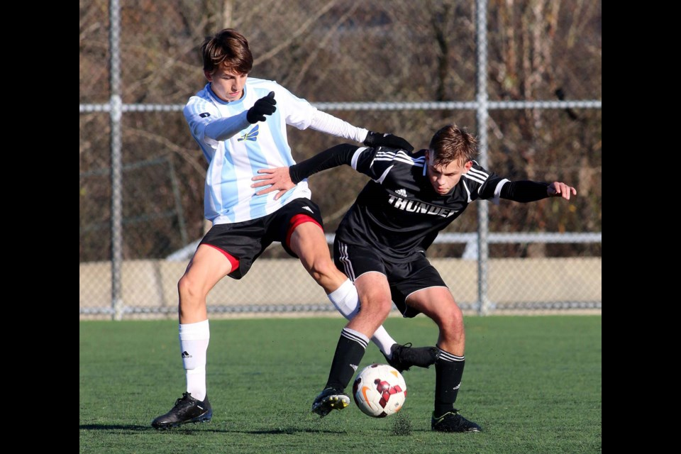 Alpha's Lucas Dasovic, at left, battles a Thomas Haney opponent for possession during early round action at the AA provincials.