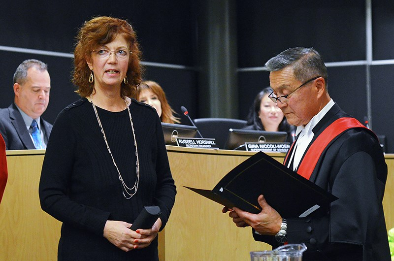 Trustee Christine Cunningham takes the oath of office with B.C. Provincial Court Judge Pedro de Couto at a public school board meeting at Burnaby Central Secondary Monday night.