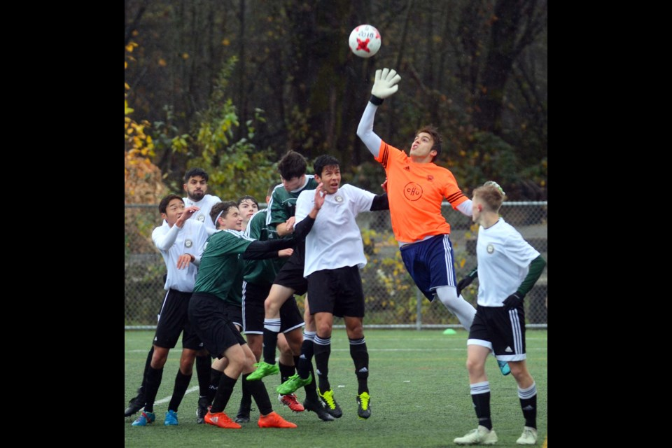 Burnaby Mountain goalkeeper Gustavo Halfen Simon gets ready to make a save while teammates Nic Riccardi, Liam Atterton, Tim Ellen and Maks Boyle, in green, and players from Abbotsford crowd the box during last Friday's game at the AAA provincial soccer championships.
