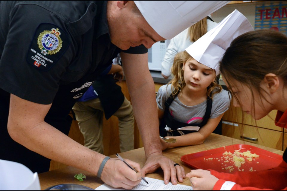 The Hot Flying Eagle Chefs, including special Const. Sheldon Frayle, Grade 4 F.W. Howay student Sienna Stewardson, centre, and Grade 5 Qayqayt student Adriana Meikle work on their recipe at the Cooking with Cops event held last week.