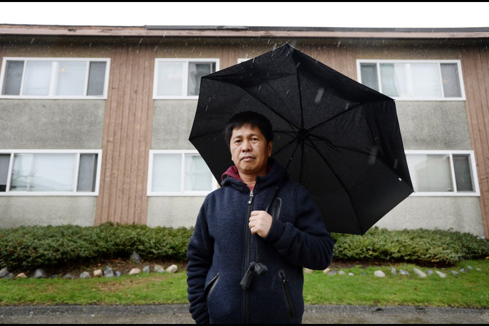 Nathan Cunan stands outside his Dow Avenue apartment building on a rainy Sunday afternoon.