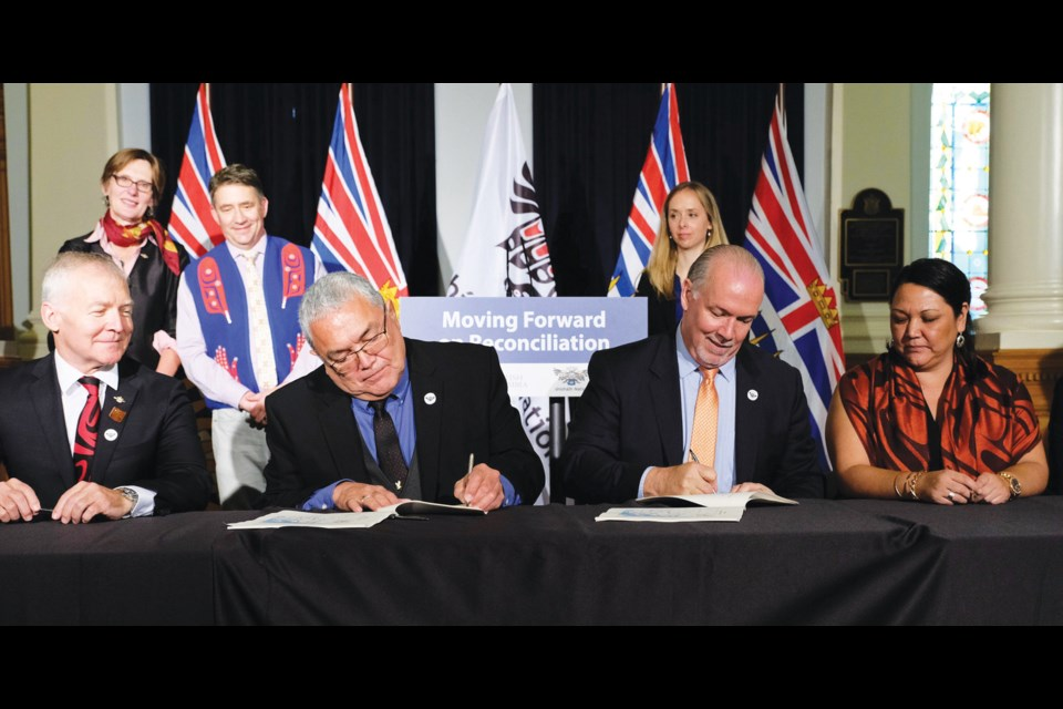 Shíshálh Nation Chief Warren Paull and Premier John Horgan sign the Foundation Agreement Oct. 4 in Victoria flanked by Scott Fraser, Minister of Indigenous Relations and Reconciliation, on the left, and shíshálh Nation Coun. Selina August on the right. Behind them stand Claire Trevena, Minister of Transportation and Infrastructure, with Sunshine Coast-Powell River MLA Nicholas Simons and Jasmine Paul, stewardship and territorial land management division manager for shíshálh Nation.