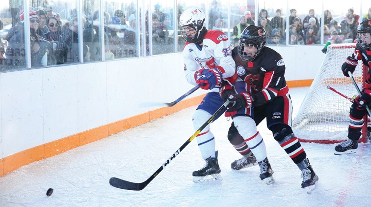Booker Daniel of the Cariboo Cougars, right, battles for the puck against Jackson Murphy-Johnson of the Vancouver Northeast Chiefs during Sunday's Winter Classic at Ernie Sam Memorial Arena, located on Nak'azdli Whut'en territory in Fort St. James. – Citizen photo by James Doyle