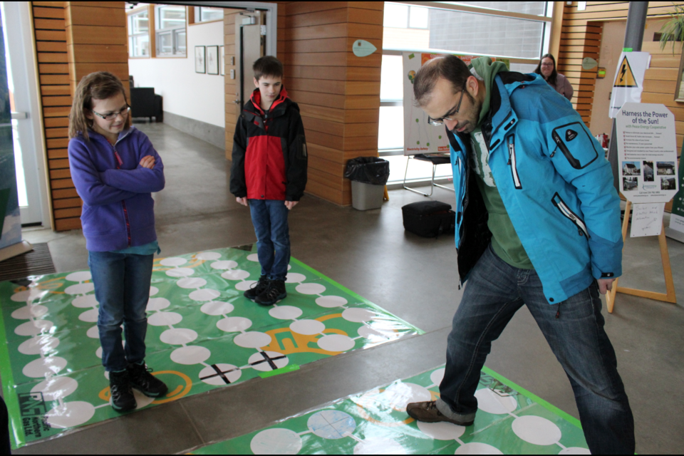 Abby, Jacob, and Jared Toth take part in a game while learning about smart energy use at Energy Explorers at Northern Lights College on the weekend.