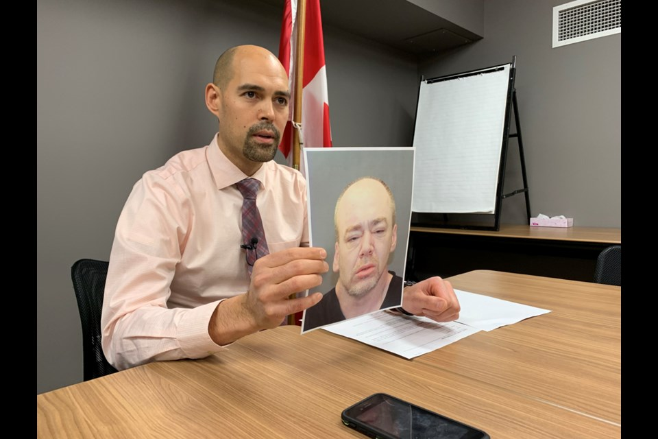 Kamloops RCMP Sgt. Nestor Baird displays a photo of murder suspect Hugh McInstosh. McIntosh and Gordon Braaten are wanted for murder and attempted murder in connection with the Feb. 15 shooting death in Brocklehurst of Jason Glover and the wounding of a woman.