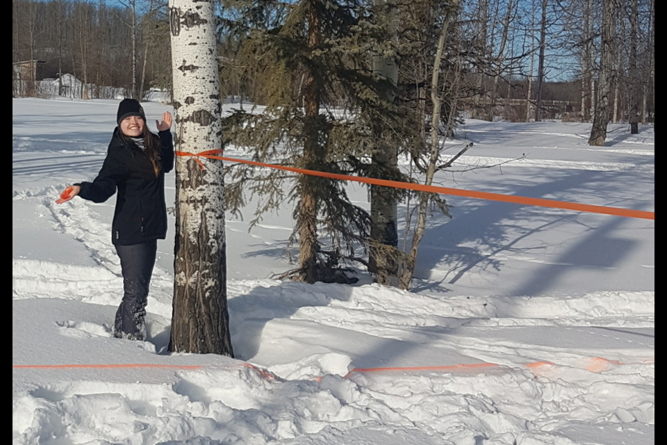 Ready to go! Village of Pouce Coupe staff member Skylar Green tying the ribbons on the finish line for the Snowmobile obstacle course at Pouce Park. Racing starts at 12 noon on March 9th.