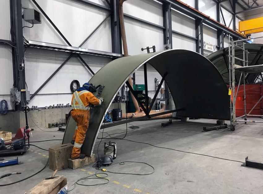 A welder works on part of a spiral case in the on-site turbines and generators manufacturing facility, January 2019.