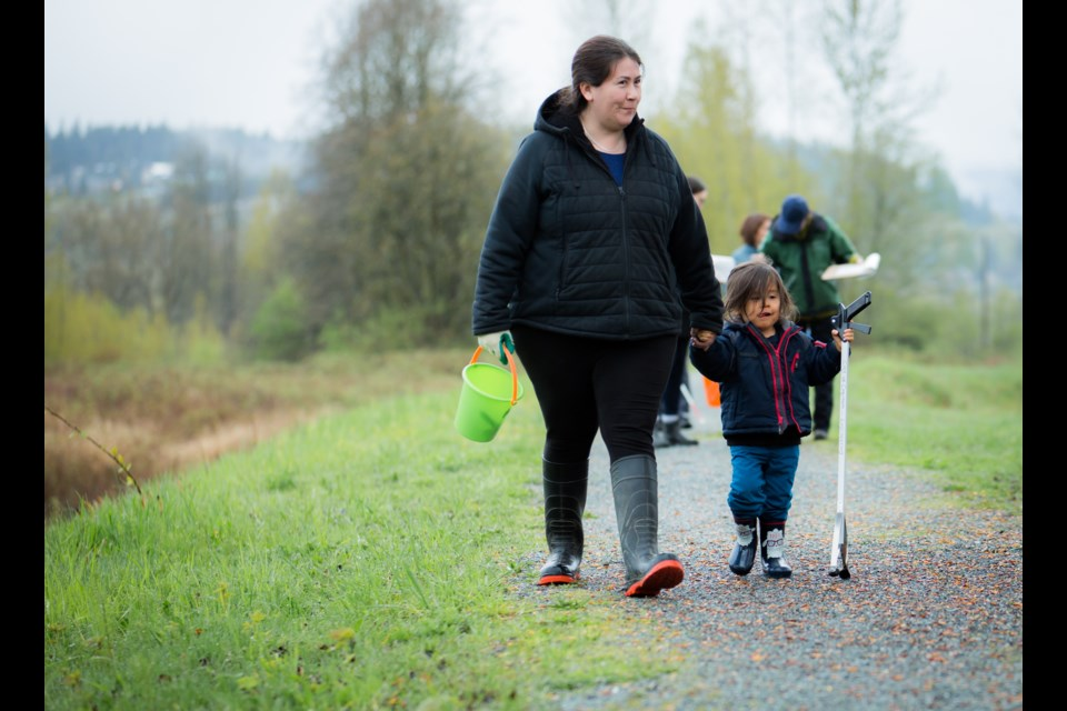 Kwikwetlem cultural leader Nancy Chaffee and her son Jamie walk along a dike of the Coquitlam River on their way to collect trash.
