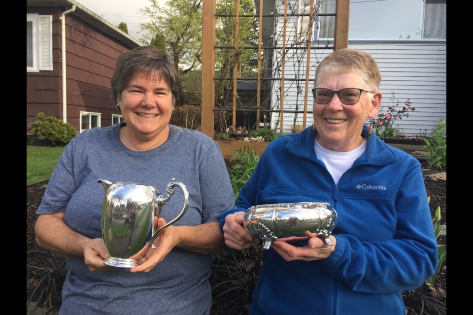 Diane Perry, left, and Audrey Barnes of the New Westminster Horticultural Society show off two of the trophies once given out to winners at the club's flower shows.