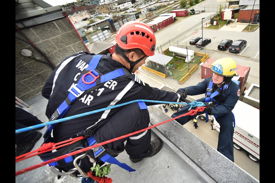 Vancouver Fire and Rescue Services training officer Christopher Won helps 17-year-old Jaden Rida to repel down a 50-foot building.