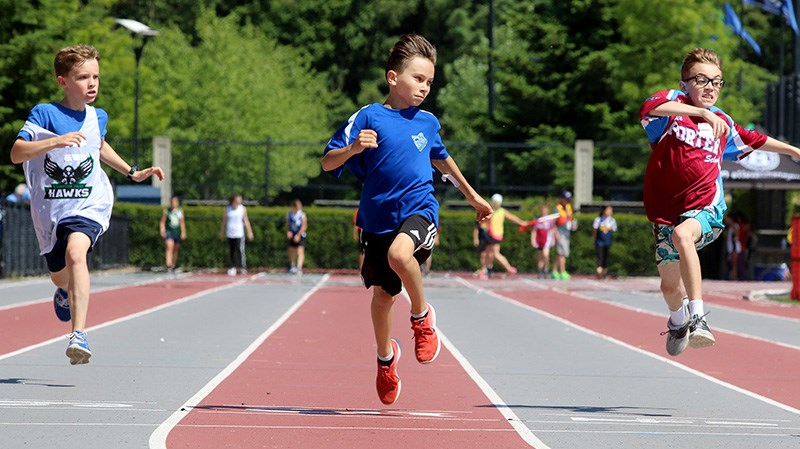 MARIO BARTEL/THE TRI-CITY NEWS Competitors in a boys 100m race leap for the finish line.