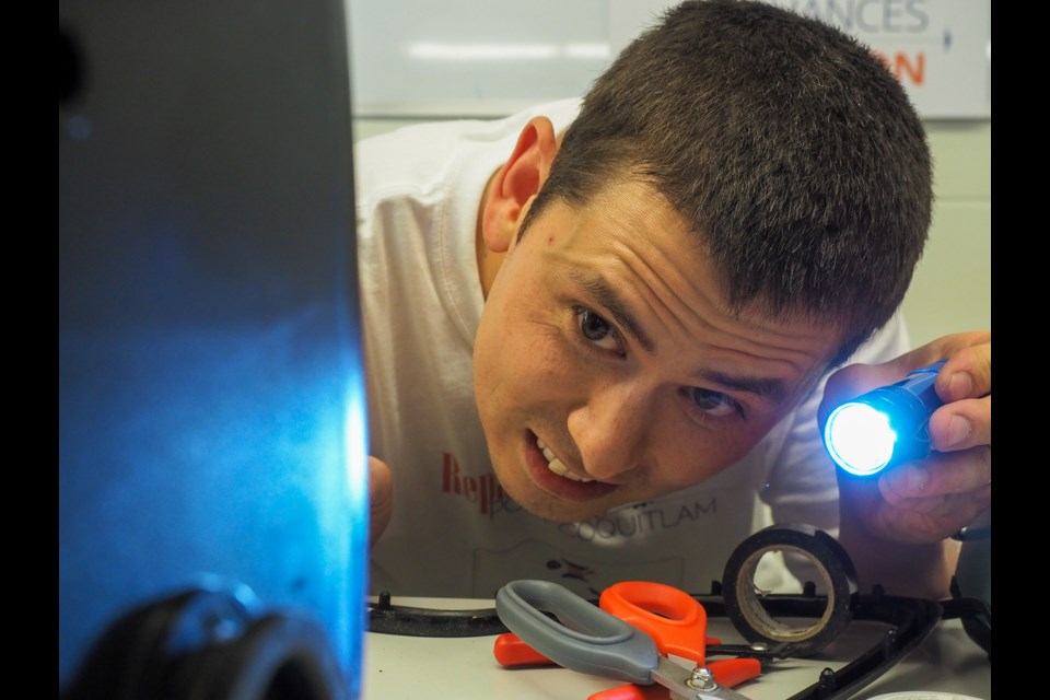 """Dan Withers peers into a screw hole after soldering the guts of a automated foot massager. An electrical engineer, Withers regularly volunteers at similar events across the Lower Mainland. """"I really enjoy it,"""" he said."""