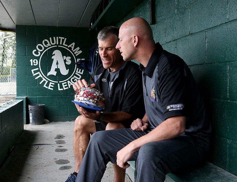 Brad Robinson, left, and Chad Hanson, reminisce about their Coquitlam A's run to the 1984 Little League World Series by looking at pins Robinson collected for his cap. The team is being honoured on Saturday with a plaque installed at Coquitlam Little League's home park, Mackin Yard.