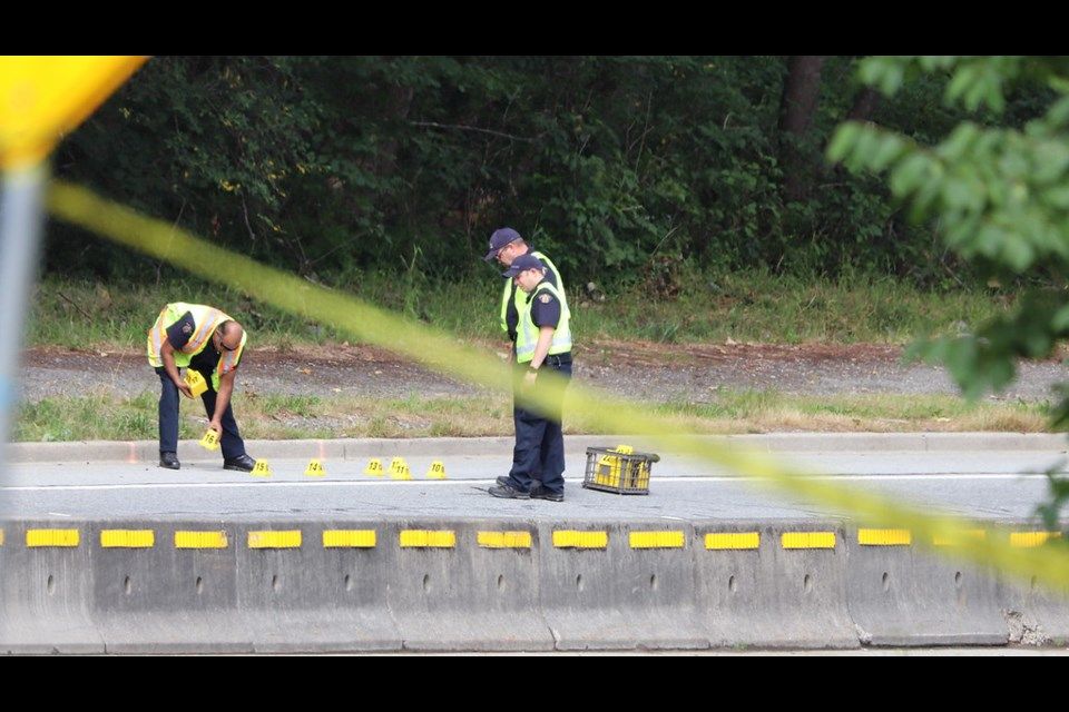 Police investigators on scene after cyclist Charles Masala was struck and killed by a driver on Gaglardi Way. SHANE MACKICHAN PHOTO