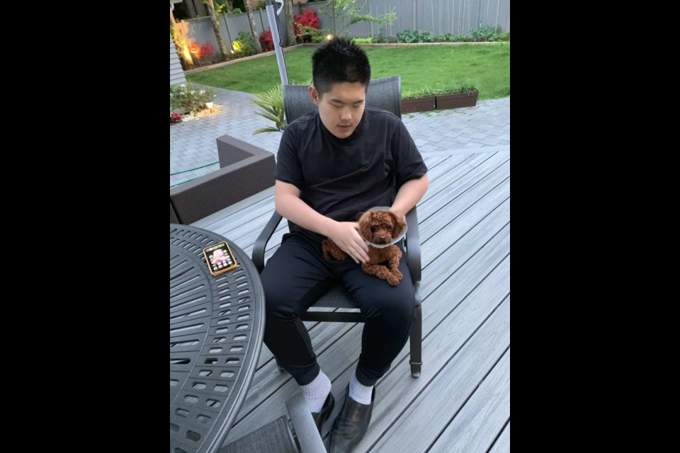 Jason Guo with his new pet Mochi pose for a photo. After losing Dora, Jason's family friends gave them a new dog to help them forget painful memories.