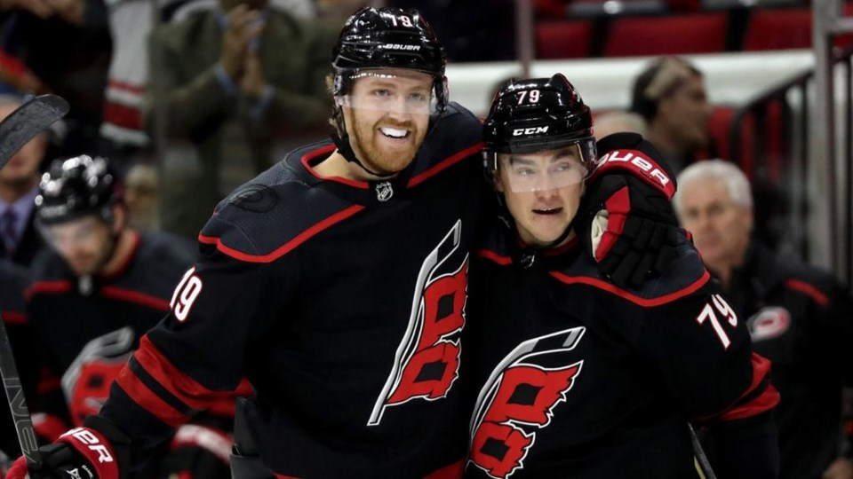 Dougie Hamilton celebrates a goal with Micheal Ferland of the Carolina Hurricanes.