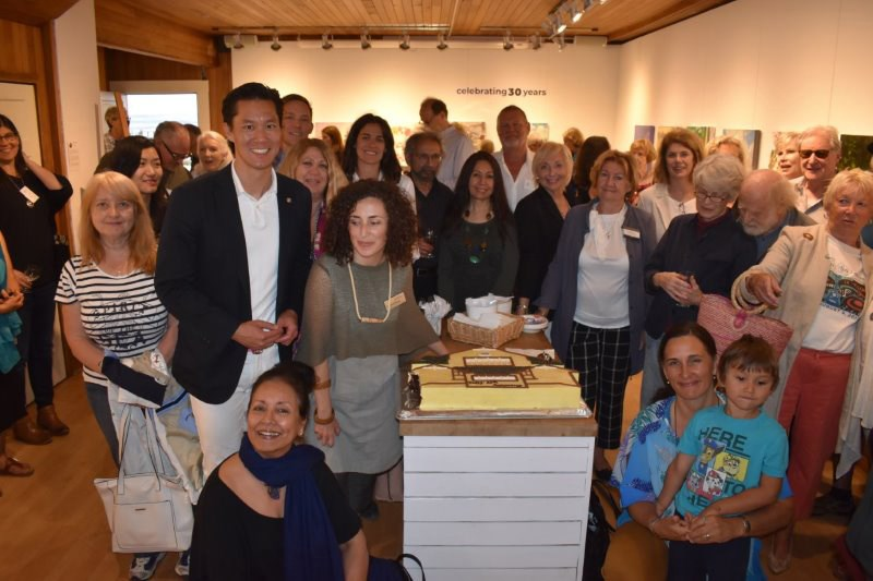 Artists, gallery staff and volunteers and attendees gather around the custom cake created by Meinhardt's for the Ferry Building Gallery's celebration on July 2.