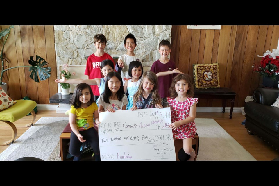 Two siblings, Bryan Zeng (rear, centre) and Ivy Zeng (middle row, right), along with their friends, raised $285 for Canucks Autism Network (CAN) from a yard sale this month. Their biggest revenue came from plants, followed by door-to-door cherry sales and a fundraising celebration party. Photo submitted