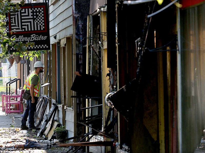 MARIO BARTEL/THE TRI-CITY NEWSTrevor Welsh, a building official with the city of Port Moody, inspects damage to buildings in the 2400-block of Clarke Street that were damaged by a fire Sunday night.