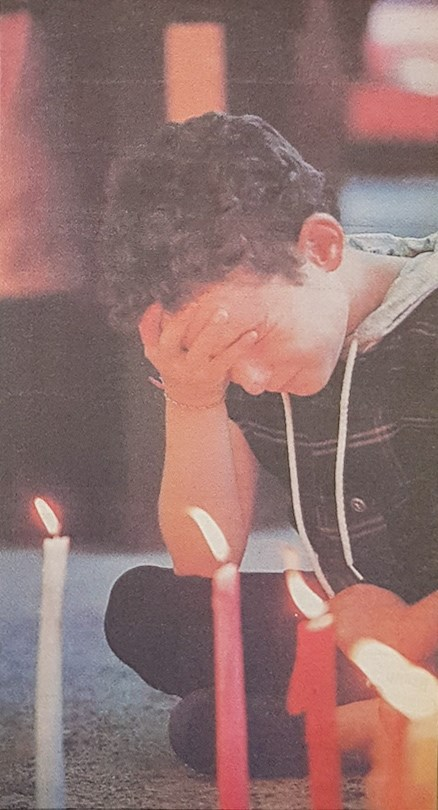 Krista Mumby, 8, Graham Niven's niece, is overcome with emotion during a candelight ceremony only a