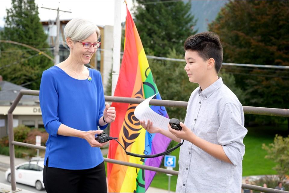 Pride Squamish member James Fujimagari reads a speech during the raising of the Squamish Pride flag ceremony, as Squamish mayor Karen Elliott looks on.